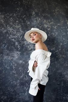 Красивая блондинка в белой рубашке и черных брюках в студии