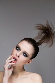 Молодая девушка с ярким макияжем и сияющей кожей.
