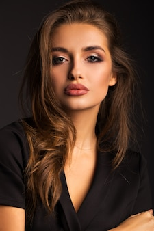 Портрет красивого брюнет на серой изолированной предпосылке. роскошная девушка с красивыми губами.