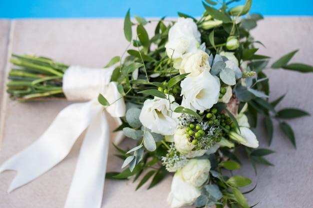 Свадебный букет невесты на синем фоне крупным планом.