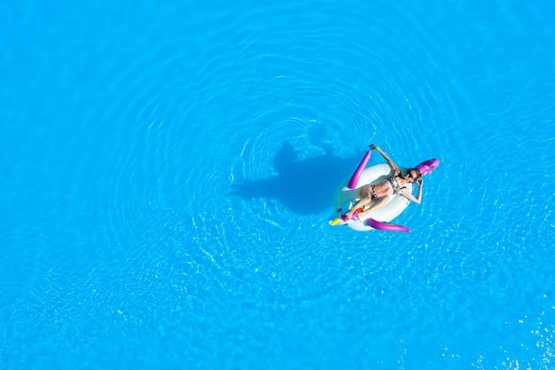 インフレータブルサークルの水着姿の女の子とプールの平面図。夏はリラックスして日焼け。