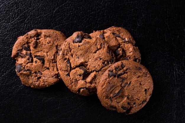 Аппетитные шоколадные печенья с кусочками изюма на черной стене.