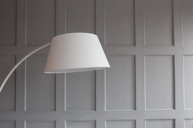 Пластиковая лампа в интерьере крупным планом. стена в стене серая. экологически чистый пластик.