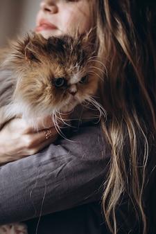 Девочка общается со своим домашним рыжим пушистым котом. любовь к животным.