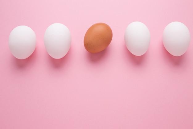 Понятие личности. коричневое яйцо среди белых яиц на розовой стене.