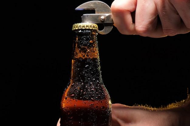 Бутылка пива с каплями воды крупным планом на черном фоне изолированных.