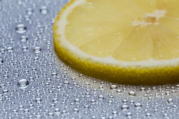 水滴のクローズアップと反射鋼のレモンのスライス
