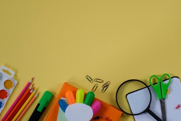 様々な学用品や黄色の背景に文房具のレイアウト。