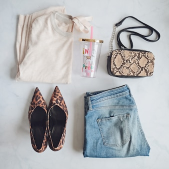 ファッション女性服セット。スタイリッシュなヘビハンドバッグクラッチ、トレンディなヒョウの靴。白い背景の上にフラットレイアウト