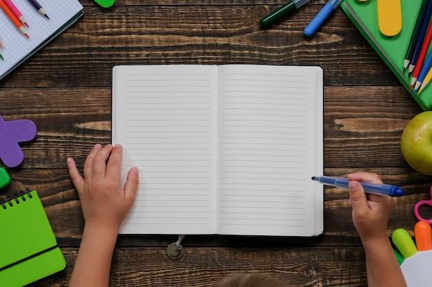 木製のテーブルに子供の手でさまざまな学用品や文房具のレイアウト。
