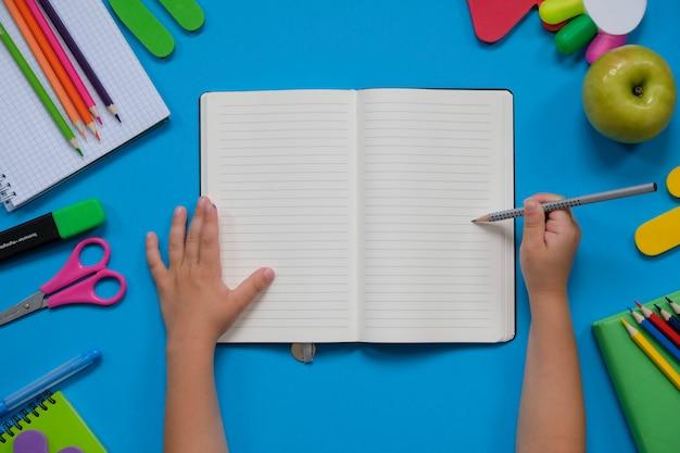 さまざまな学用品や子供の手を使った文房具のレイアウト