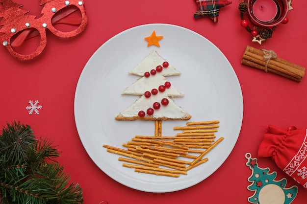 背景が赤の白い皿の上の果実で飾られたクリームチーズとパンから作られたツリー。