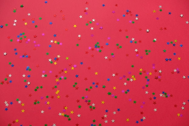 赤のトレンディな背景にカラフルな星あなたのプロジェクトのお祭りの背景