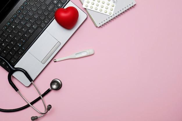 聴診器、ノート、事務用品、コピースペースとドクターピンクのテーブルとフラットレイアウト