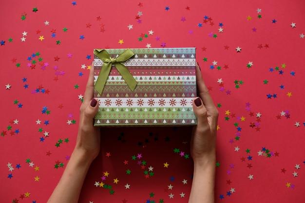 梨花の手がクリスマスプレゼントやプレゼントボックスを赤の背景に飾られて