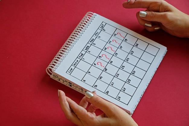 欠落した期間とカレンダー上のマーキング。望まない妊娠と月経の遅れ。