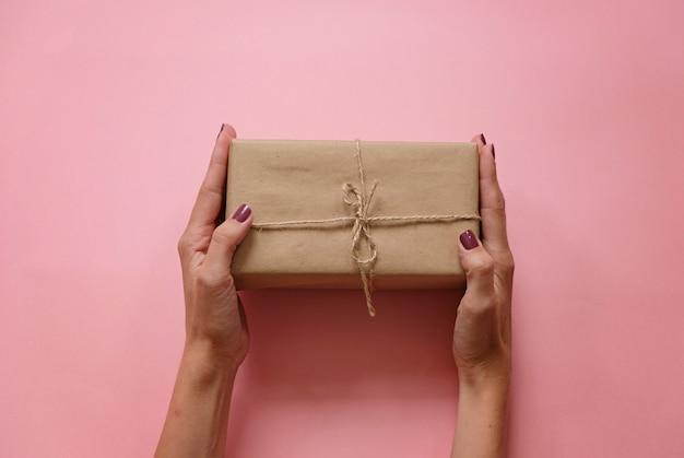 梨花の手がピンクのパステル調の背景トップビューにギフトまたはプレゼントボックス