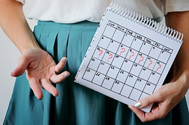 マークされた逃した期間でカレンダーを保持している女性。望まない妊娠、女性の健康、月経の遅れ。