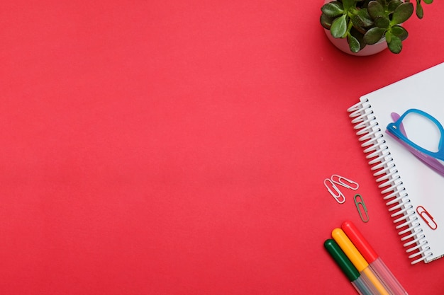 オフィスの文房具とフラットレイアウトワークスペース赤いデスク。ビジネス女性ブログヒーローコンセプト。