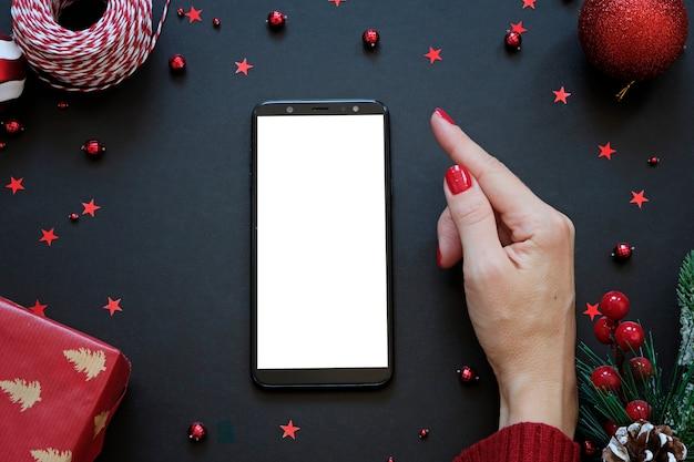 黒と赤のクリスマス組成の真ん中にスマートフォン