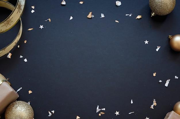 金色の装飾と黒のお祭りの背景。テキストのための場所でクリスマスのグリーティングカード
