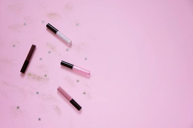 ピンクの背景にリップクリームとフラットレイアウト