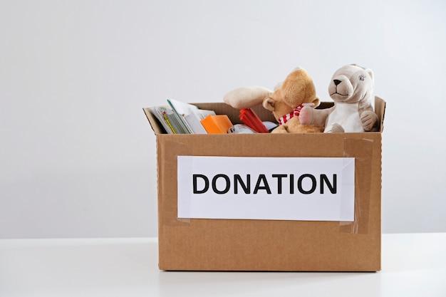 寄付のコンセプト。本と白いテーブルの上のおもちゃでいっぱいのボックス。子供のために寄付してください