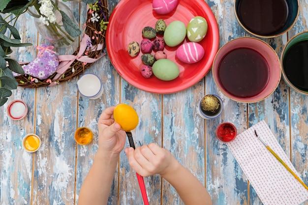 卵の染料でイースターエッグを着色子供の手のクローズアップ。上からの眺め