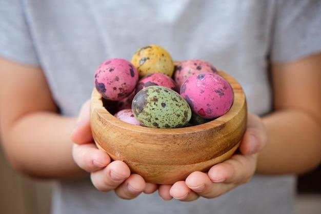 イースターの子供の手でボウルに塗られたウズラの卵