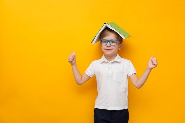Милый маленький школьник в очках, держа книгу на голове