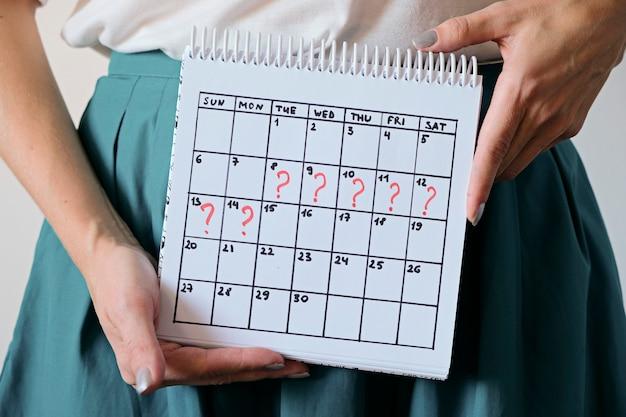 Женщина, держащая календарь с отмеченным пропущенным периодом. нежелательная беременность, здоровье женщины и задержка менструации.
