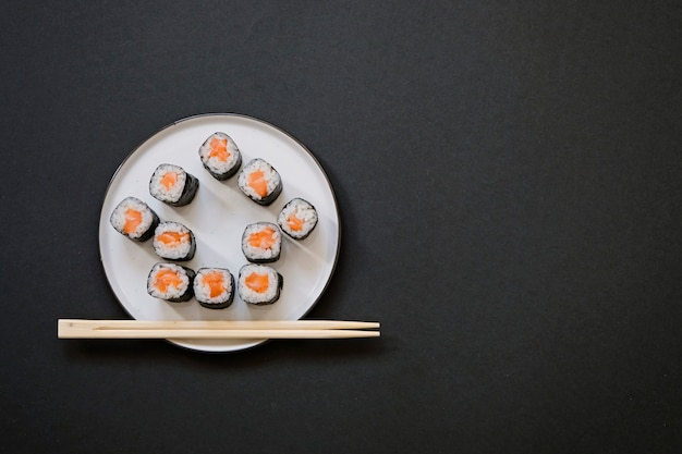 家の形のコピースペースと黒の背景には箸で巻き寿司