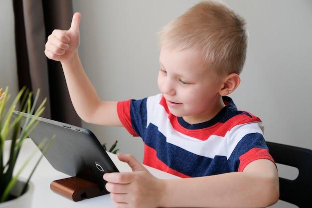 Дистанционное обучение онлайн-образование. милый кавказский мальчик делая домашнюю работу с пк таблетки дома