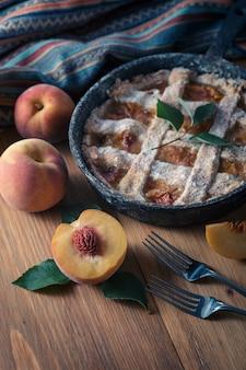 Персиковый пирог в чугунной сковороде лежит на деревянном столе.