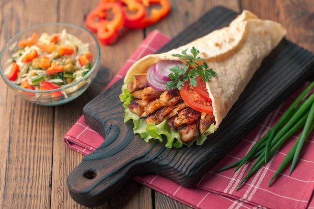 ドネルケバブはまな板の上に横たわっています。鶏肉、玉ねぎ、サラダとシャワルマは暗い古い木製のテーブルにあります。