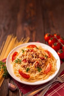 トマトソースとひき肉、すりおろしたパルメザンチーズと新鮮なパセリのパスタボロネーゼ-自家製の健康的なイタリアンパスタ