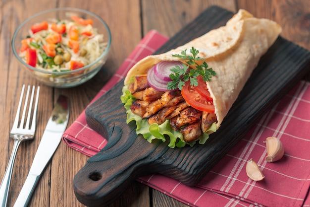 Донер кебаб лежит на разделочной доске. шаурма с куриным мясом, луком, салатом лежит на темном старом деревянном столе.