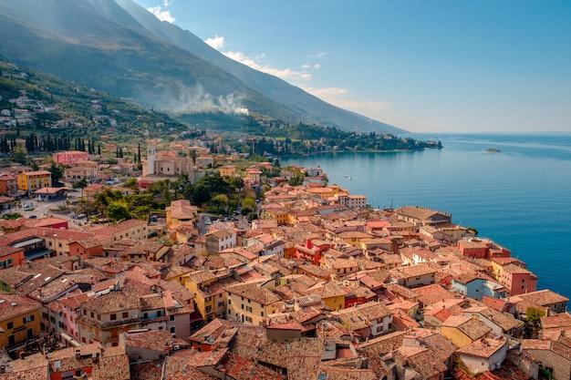 Вид на озеро гарда с башни в городе мальчезине. италия. вид на черепичные крыши итальянского города. озеро гарда. рива дель гарда.