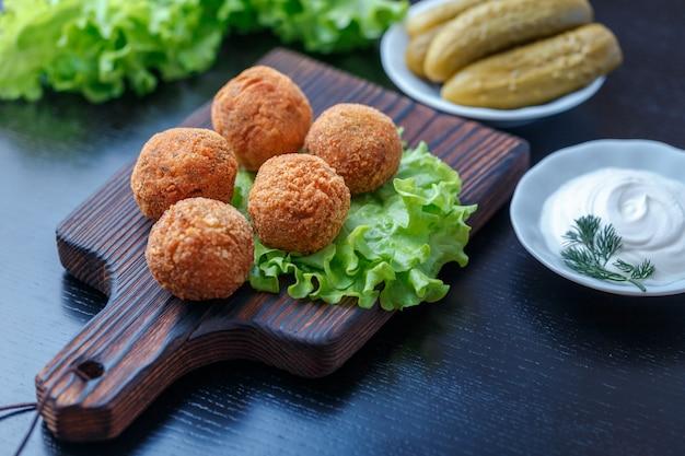 ファラフェルは木製のまな板の上にあります。テーブルの上にはトマト、きゅうり、レタス、ディル、レモン、サワークリームがあります。中東の郷土料理。