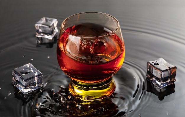 ワイングラスと赤ワインのボトル。水のしぶきと黒い反射の液滴。