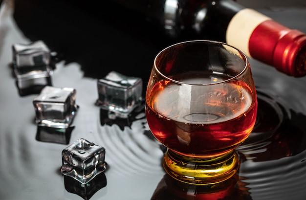 Бутылка красного вина с рюмкой. всплеск воды и капли на черном отражении.