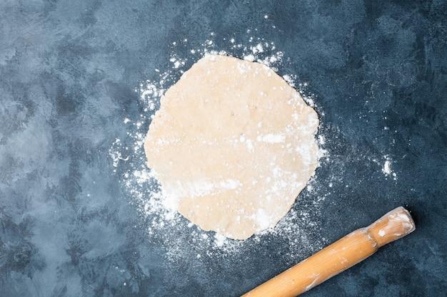 Роллинг тесто на столе с деревянной скалкой.