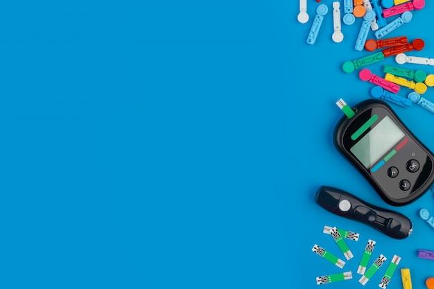 グルコメーター。血糖値を測定するためのデバイス。テストストリップ、青色の背景に丸薬。