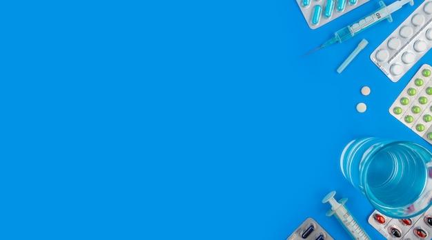 Цветные таблетки и таблетки на синем фоне с копией пространства