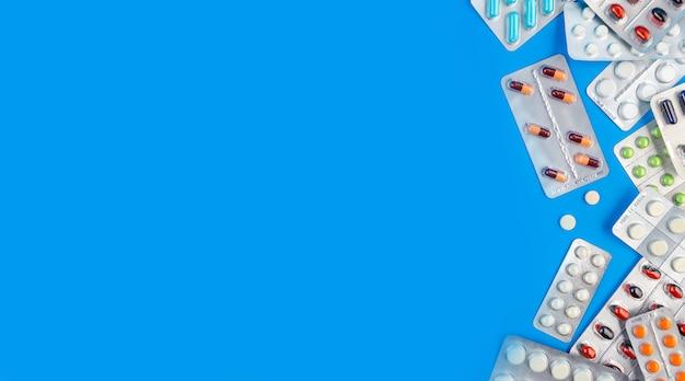 着色された丸薬と錠剤コピースペースと青色の背景に