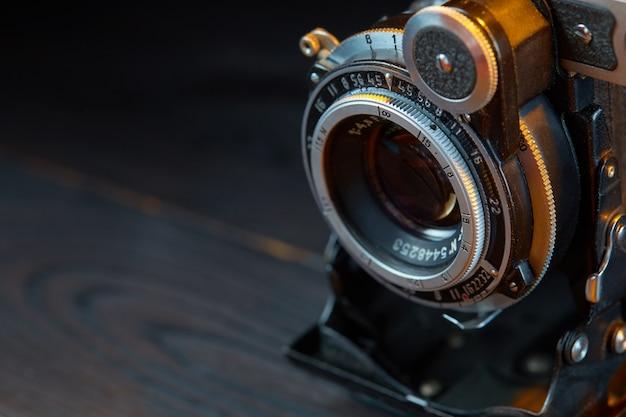木製のテーブルに古いビンテージカメラ。映画のようなスタイル。