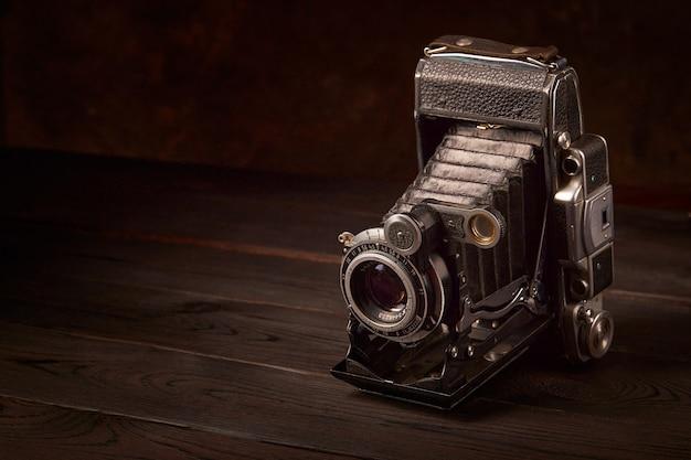 Старая винтажная камера на деревянном столе. кинематографический стиль.