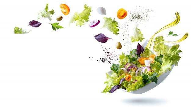 Белая тарелка с салатом и плавающими в воздухе ингредиентами: оливки, салат, лук, помидор, сыр моцарелла, петрушка, базилик и оливковое масло.