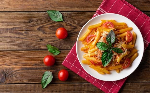 トマトソースとミンチ肉のパスタボロネーゼ、パルメザンチーズのすりおろした新鮮なバジル - 素朴な木製の自家製健康的なイタリアンパスタ。平らに置きます。上面図。