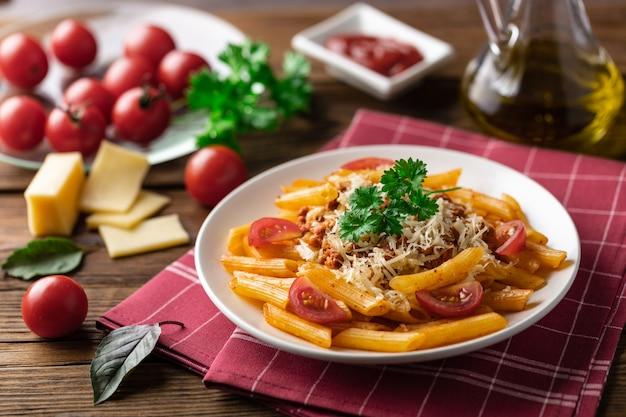 トマトソースとミンチ肉のパスタボロネーゼ、パルメザンチーズのすりおろした新鮮なバジル - 素朴な木製の自家製健康的なイタリアンパスタ。